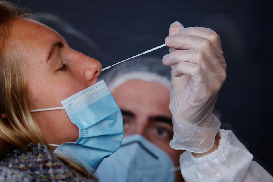 A health worker administers a nasal swab to a patient at a coronavirus testing site in Lille, France,: REUTERS