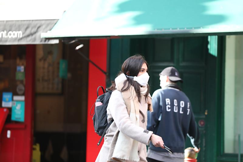 A pedestrian in London wears a protective facemask on the day that Heath Secretary Matt Hancock said that the number of people diagnosed with coronavirus in the UK has risen to 51.