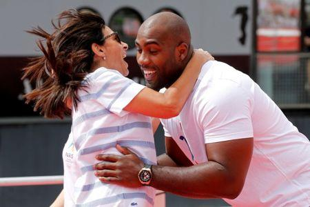 Olympic Judo champion Teddy Riner and Paris Mayor Anne Hidalgo react on an athletics track installed on the River Seine in Paris, France, June 23, 2017 as Paris transforms into a giant Olympic park to celebrate International Olympic Days with a variety of sporting events for the public across the city during two days as the city bids to host the 2024 Olympic and Paralympic Games.  REUTERS/Jean-Paul Pelissier