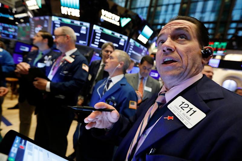 Tommy Kalikas, right, works with fellow traders on the floor of the New York Stock Exchange during the Brigham Minerals IPO, Thursday, April 18, 2019. U.S. stock indexes wavered between modest gains and losses in midday trading Thursday as another slide in health care sector companies offset gains elsewhere in the market. (AP Photo/Richard Drew)