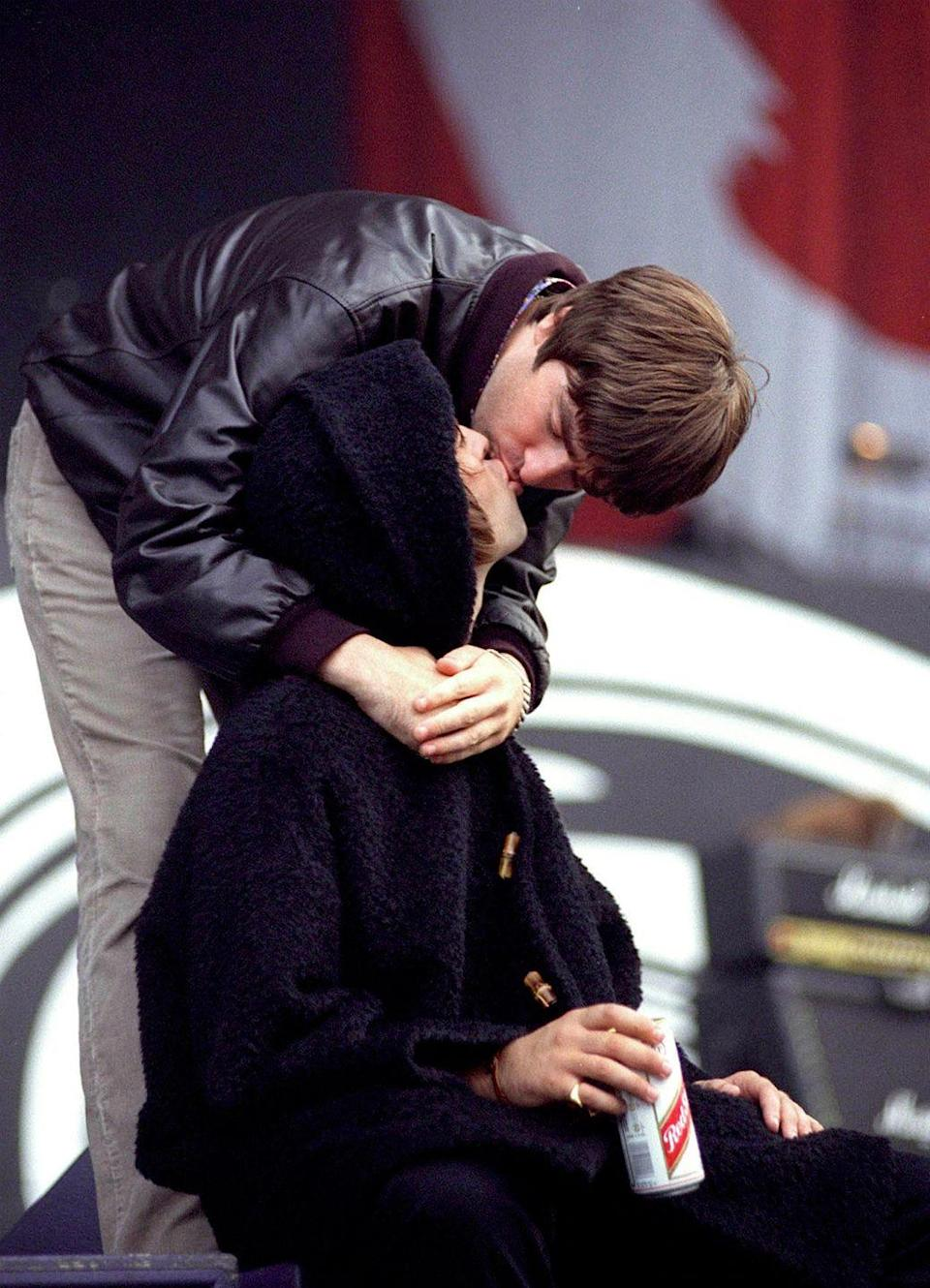 <p>Noel and Liam kissing on stage at Glasgow Green Festival in 2000.</p>