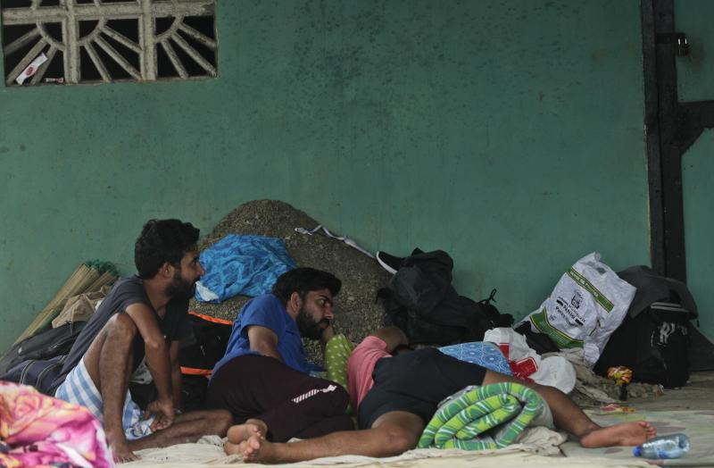 A group of migrants rest on the ground in the Peñitas Humanitarian camp prior a visit of Acting U.S. Homeland Security Secretary Kevin McAleenan, in Peñitas, Panama, Friday, Aug. 23, 2019. (AP Photo/Arnulfo Franco)