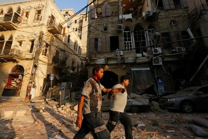A wounded man is helped as he walks through debris in Beirut's Gemmayzeh district following the twin explosions (AFP Photo/Marwan TAHTAH)