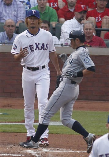 Seattle Mariners Ichiro Suzuki (51) of Japan crosses home plate scoring in front of Texas Rangers starting pitcher Yu Darvish (11) of Japan during the first inning of a baseball game Monday, April 9, 2012 in Arlington, Texas. (AP Photo/LM Otero)