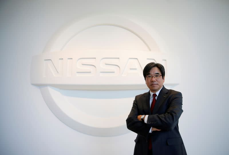 FILE PHOTO: Nissan Executive Vice President Sakamoto poses with the carmaker's logo in the showroom at the carmaker's headquarters in Yokohama