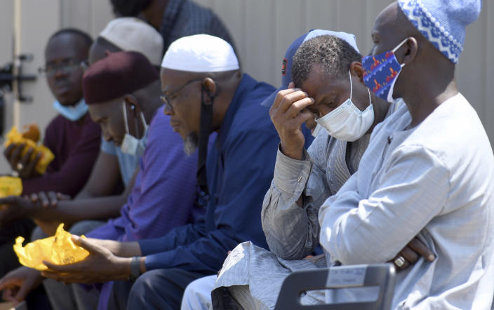 Men from West Africa sit near the site where five people were found dead after a house fire in suburban Denver, Wednesday, Aug. 5, 2020. Three people escaped the fire by jumping from the home's second floor. Investigators believe the victims were a toddler, an older child and three adults. (AP Photo/Thomas Peipert)