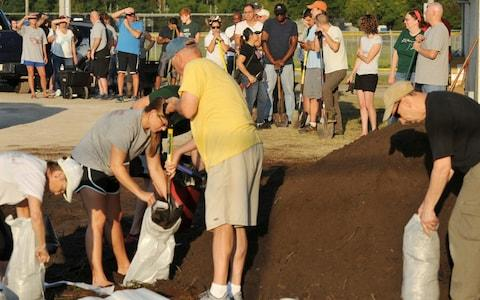 St Johns County Florida residents wait for the arrival of sandbags - Credit:  Bob Self/AP