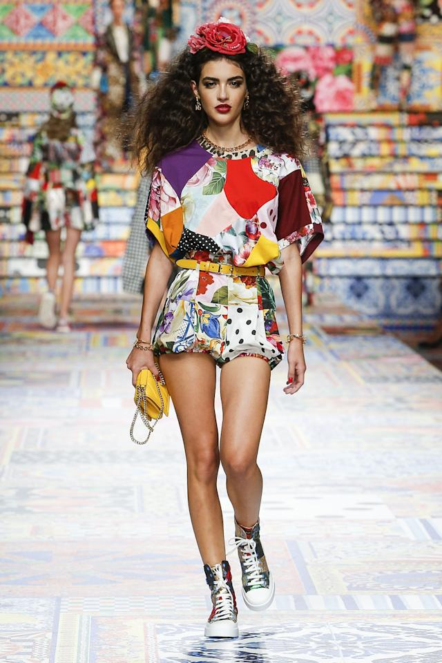 """<p>Weaving together the history of Italy would take a lifetime, but Dolce & Gabbana attempted it in one collection. On their SS21 runway the theme was clear: Patchwork is going to be big. The designers referenced their own backlog, noting their spring 1993 runway as part of their own inspiration. Both collections heavily plucked details from the '70s, but today's presentation felt refreshingly modern. </p><p>Inspired and dedicated to the city of Sicily, Dolce & Gabbana wanted to capture the spirit of Italian artistry with  <em>""""fatto a mano,"""" </em>or handmade craftsmanship. Within each patchwork look—and there were <em>many </em>in this 98-look collection— was a demi-couture approach of one-of-a-kind pieces that literally and figuratively thread together the past with the present. Fabrics from the brand's archives were interwoven with freshly acquired textiles. The result was a mix of polka dots, floral brocades, denim, and more, cut together in a multitude of silhouettes for every fit and fancy. The chaotic richness was a whirlwind of details that span decades, but their hashtag  <a href=""""https://www.instagram.com/explore/tags/dgsicilianpatchwork/"""">#DGSicilianPatchwork</a> brought it into 2020. </p><p><em><em>Click through to see every look from Dolce & Gabbana's spring-summer 2021 runway show.</em></em></p>"""