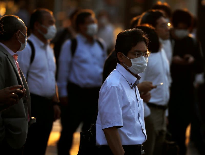 FILE PHOTO: Office workers wearing protective face masks walk to head home at sunset amid the coronavirus disease (COVID-19) outbreak, in Tokyo