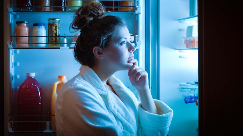 A young dieting woman standing in front of the refrigerator, contemplating and thinking about what to eat for hunger. Making choices and decision for healthy lifestyle