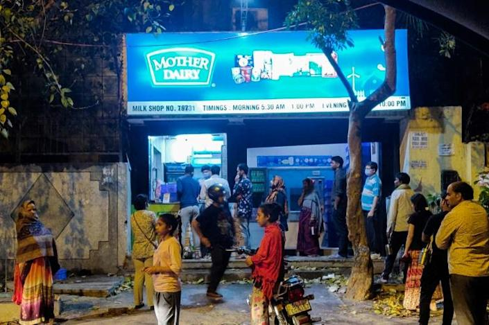 People line up at a dairy shop to buy milk in New Delhi on March 24 (AFP Photo/Aishwarya KUMAR)