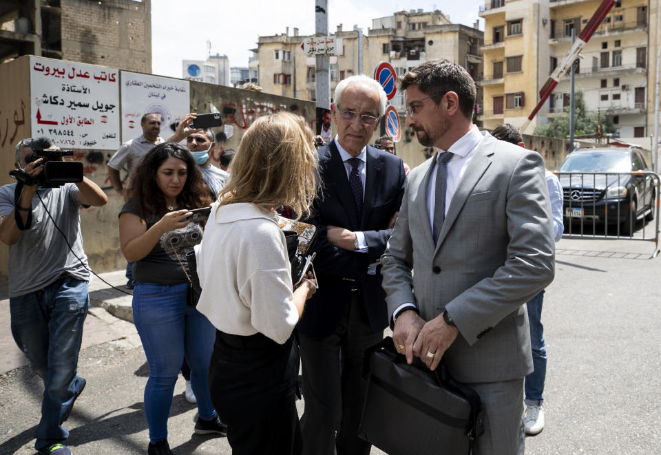 """Members of Carlos Ghosn's defense team, lawyer Jean Yves Le Borgne, center, and Jean Tamalet, right, leave the Justice Palace in Beirut, Lebanon, Friday, June 4, 2021. Lawyers of Ex-Nissan boss Carlos Ghosn said on Friday their client has answered hundreds of questions by French and Lebanese investigators over the past week describing him as """"happy and satisfied"""" to be given the opportunity to explain himself over accusations of financial misconduct. (AP Photo/Hassan Ammar)"""