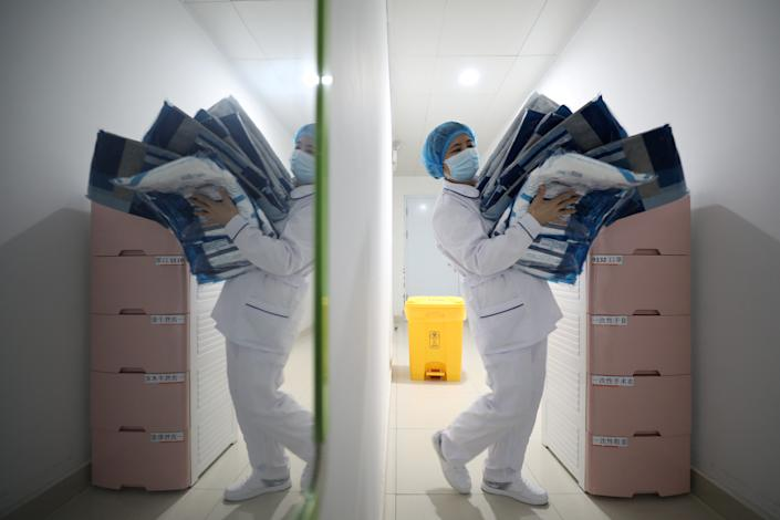 Medical worker carries protective suits at Jinyintan hospital in Wuhan, the epicenter of the novel coronavirus outbreak
