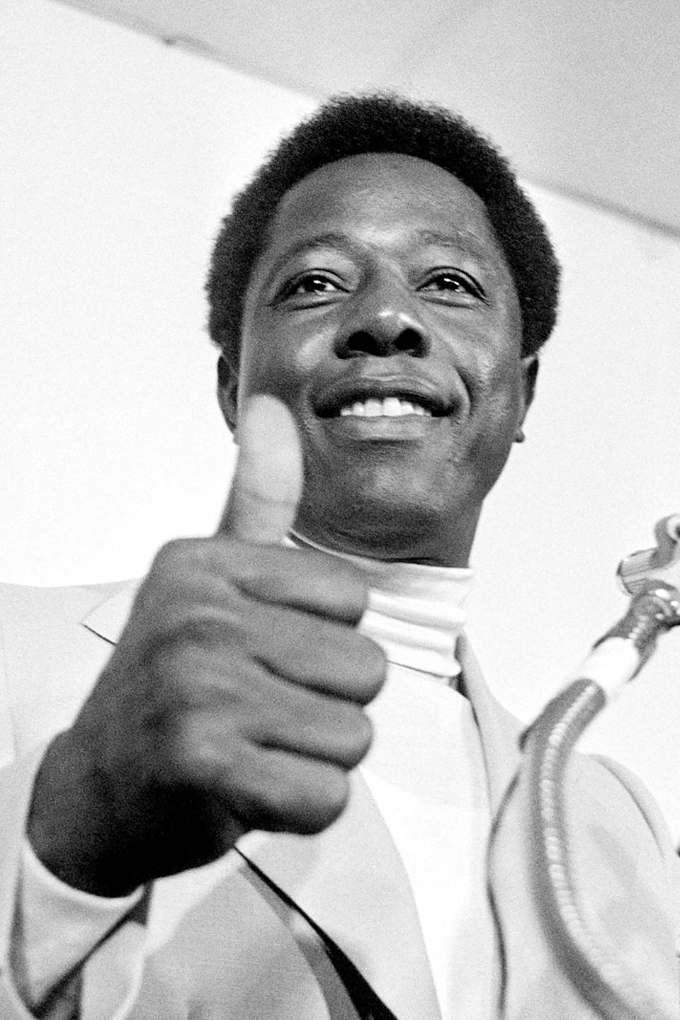 FILE - Atlanta Braves' Hank Aaron gives the thumbs-up sign to reporters indicating he will play in the season opener against the Cincinnati Reds at Riverfront Stadium in Cincinnati, in this April 4, 1974, file photo. Hank Aaron, who endured racist threats with stoic dignity during his pursuit of Babe Ruth's home run record and gracefully left his mark as one of baseball's greatest all-around players, died Friday. He was 86. The Atlanta Braves, Aaron's longtime team, said he died peacefully in his sleep. No cause was given.(AP Photo/File)
