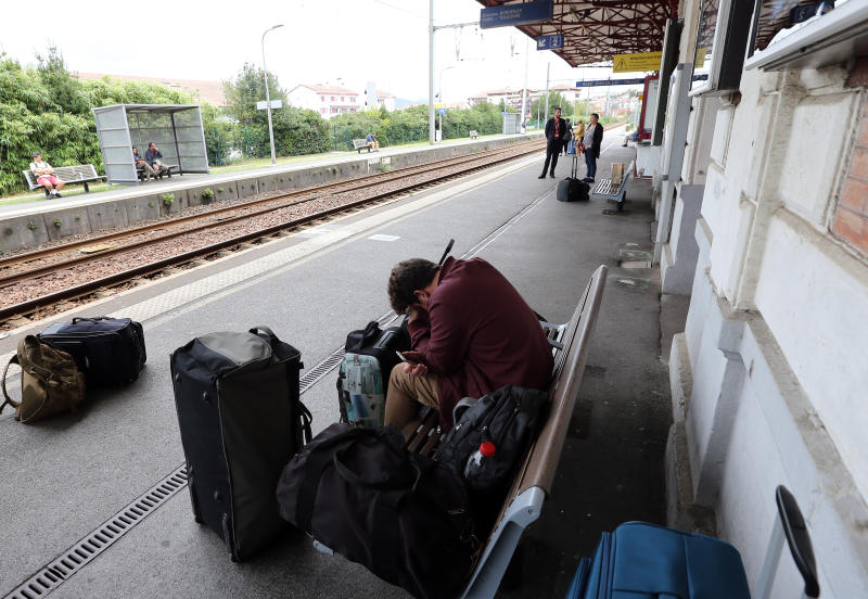 A traveler sleeps on the platform of the station of Saint Jean de Luz, southwestern France, Friday, Oct.18, 2019. A wildcat strike is disrupting train travel around France, as railway workers demand better security after a recent accident. (AP Photo/Bob Edme)