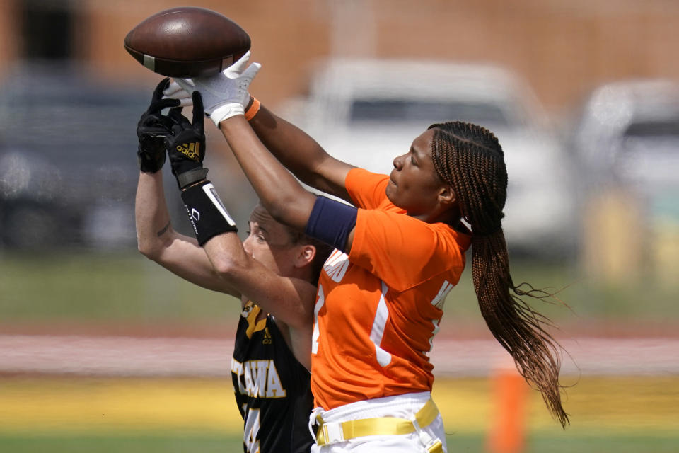 Midland receiver JaNasia Spand, right, and Ottawa defender Jennifer Anthony (14) reach for the ball during an NAIA flag football game in Ottawa, Kan., Friday, March 26, 2021. The National Association of Intercollegiate Athletics introduced women's flag football as an emerging sport this spring. (AP Photo/Orlin Wagner)