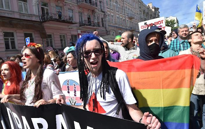 Members of LGBT community shout slogans and carry banners as they march during a 2016 gay pride parade in Kiev (AFP Photo/SERGEI SUPINSKY )