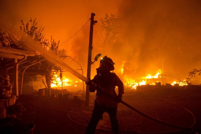FILE - In this Aug. 12, 2020, file photo, a firefighter works against the Lake Hughes Fire in Angeles National Forest north of Santa Clarita, Calif. Firefighters are struggling to contain three wildfires near Los Angeles as forecasters warn that the risk of new fires was high with temperatures expected to spike and humidity levels to drop across California. (AP Photo/Ringo H.W. Chiu, File)