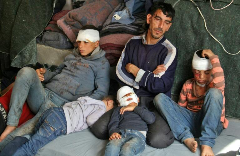Syrians, who were wounded in a suicide car bombing that hit buses carrying evacuees from besieged government-held towns, sit in a tent on the Syrian-Turkish border on April 17, 2017