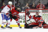 New Jersey Devils goaltender Louis Domingue (70) makes a save during the second period of the team's NHL hockey game against the Montreal Canadiens, Tuesday, Feb. 4, 2020, in Newark, N.J. Canadiens left wing Ilya Kovalchuk (17) and Devils defenseman Will Butcher watch. (AP Photo/Kathy Willens)