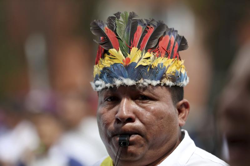 An indigenous man blows on a whistle during a national strike in Bogota, Colombia, Wednesday, Dec. 4, 2019. Colombia's recent wave of demonstrations began with a massive strike on Nov. 21 that drew an estimated 250,000 people to the streets. Protests have continued in the days since but at a much smaller scale. (AP Photo/Fernando Vergara)