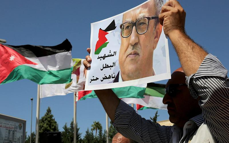 Relatives of Jordanian writer Nahed Hattar hold up signs protesting his death, in front of Jordanian Prime Ministry in Amman, Jordan, September 2016 - Credit:  Raad Adayleh/AP