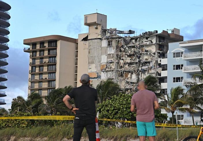 People look at the rubble at Champlain Towers South Condo in Surfside, located at 8777 Collins Avenue. Part of the building collapsed in the early morning of Thursday, June 24, 2021.
