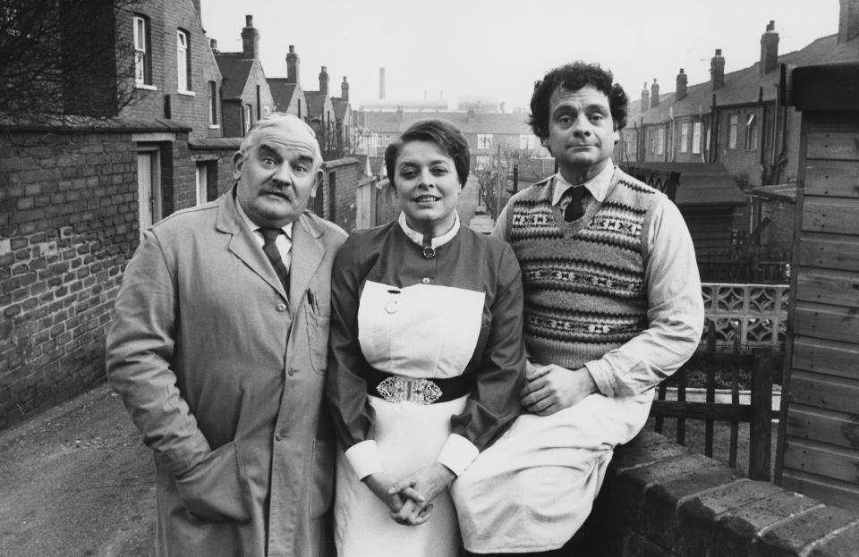 Portrait of actors (L-R) Ronnie Barker, Lynda Baron and David Jason standing in a back alley, photographed for Radio Times in connection with the television sitcom 'Open All Hours', South Yorkshire, January 30th 1981. (Photo by Don Smith/Radio Times/Getty Images)