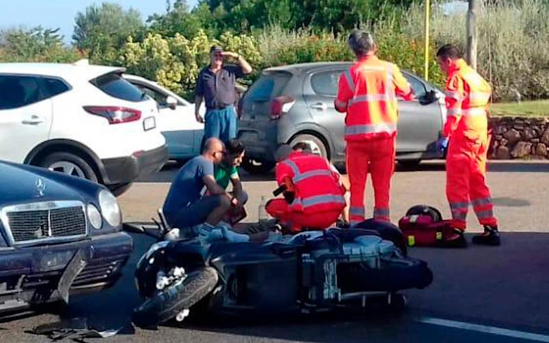 Ambulance personnel tend to a man lying on the ground, later identified as actor George Clooney, after the accident near Olbia in Sardinia - AP