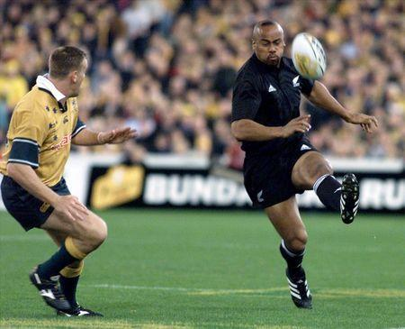 New Zealand's Jonah Lomu (R) kicks the ball past Australia's Chris Latham during their rugby union Tri Nations test in Sydney September 1, 2001. REUTERS/Mark Baker