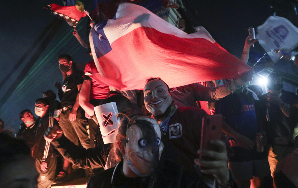 People gather at Plaza Italia on the day Chileans voted in a referendum to decide whether the country should replace its 40-year-old constitution, written during the dictatorship of Gen. Augusto Pinochet, in Santiago, Chile, Sunday, Oct. 25, 2020. (AP Photo/Esteban Felix)