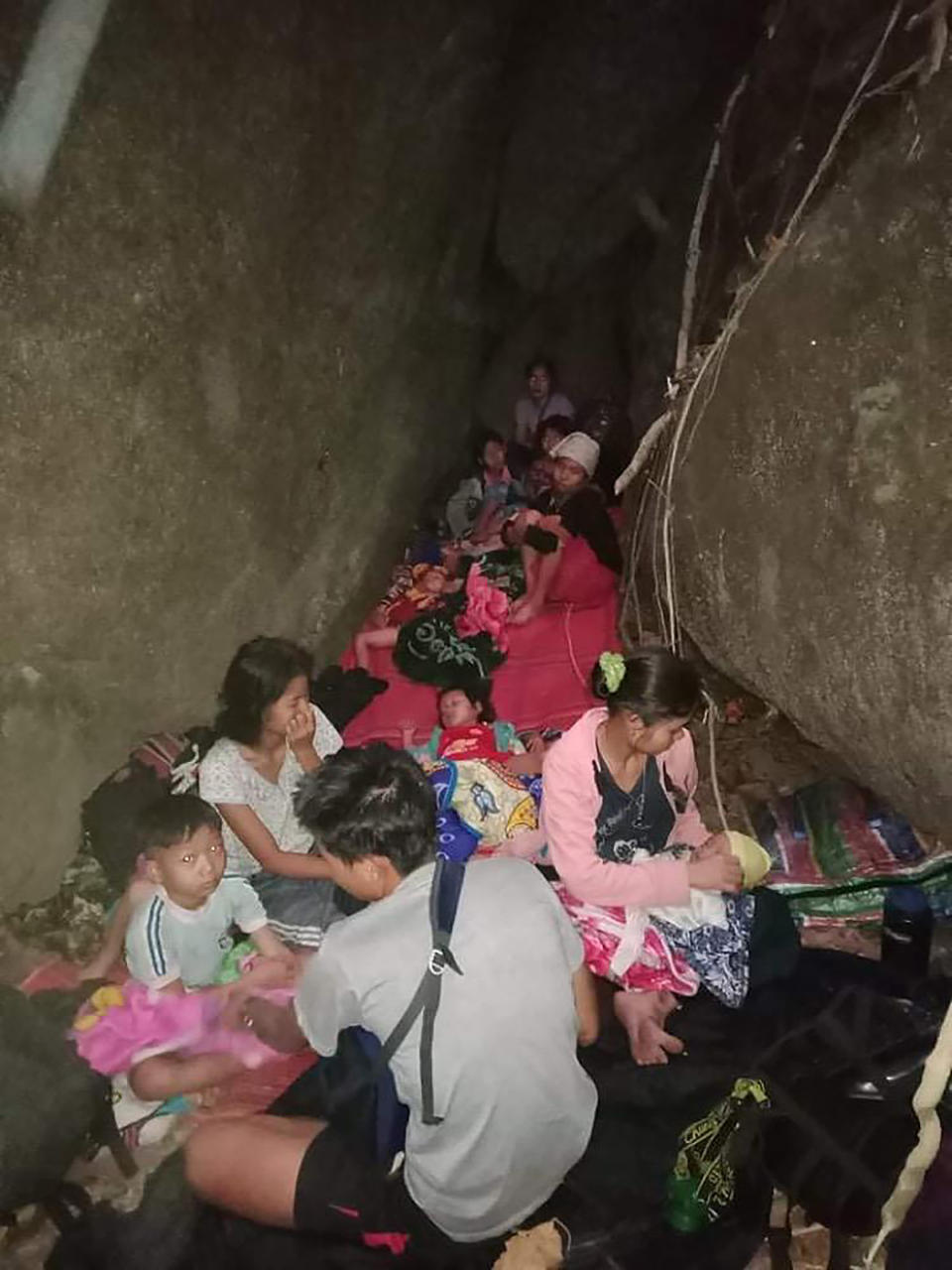 In this photo provided by Free Burma Rangers, villagers shelter in the open due to airstrikes, Saturday, March 27, 2021, in Deh Bu Noh, in Karen state, Myanmar. Myanmar military jets hit a village in Karen State, on Saturday night, killing a few people and wounding others, according to relief organizations.(Free Burma Rangers via AP)