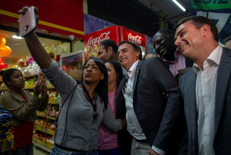 Brazilian presidential candidate Jair Bolsonaro (PSL), accompanied by his son Flavio (R), senate candidate for the state of Rio de Janeiro, visits the Mercadao de Madureira, in Rio de Janeiroon August 27, 2018. Bolsonaro is polling in second place for the October 7 first round of voting, after imprisoned frontrunner Luiz Inacio Lula da Silva, and followed by center-right former Sao Paulo governor Geraldo Alckmin and environmentalist Marina Silva