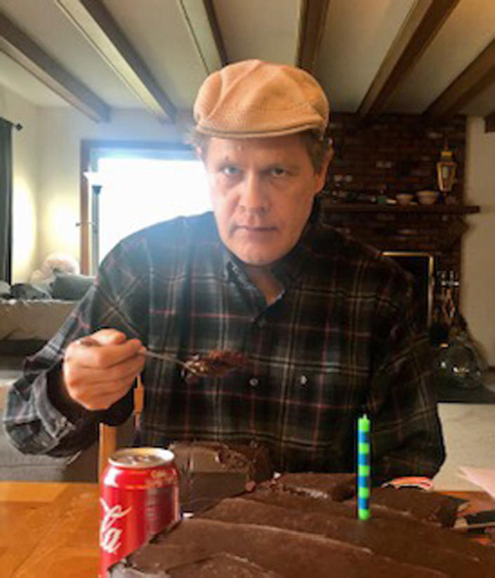 In this photo provided by Vedanta Griffith, Joshua Spriestersbach enjoys birthday cake on April 12, 2020, in Danby, Vt. The Hawaii Innocence Project says, Monday, Aug. 2, 2021, Spriestersbach was wrongfully arrested for someone else's crime and then committed to a state hospital for more than two years because officials mixed him up with someone else. (Vedanta Griffith via AP)