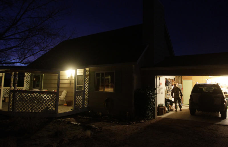 In this Nov. 30, 2012 photo, 1st Lt. Aaron Dunn enters his home before sunrise on the morning of his return from a deployment in Afghanistan, in Fountain, Colo. Many soldiers returning home after long deployments describe the change as welcome, but also overwhelming at first. (AP Photo/Brennan Linsley)