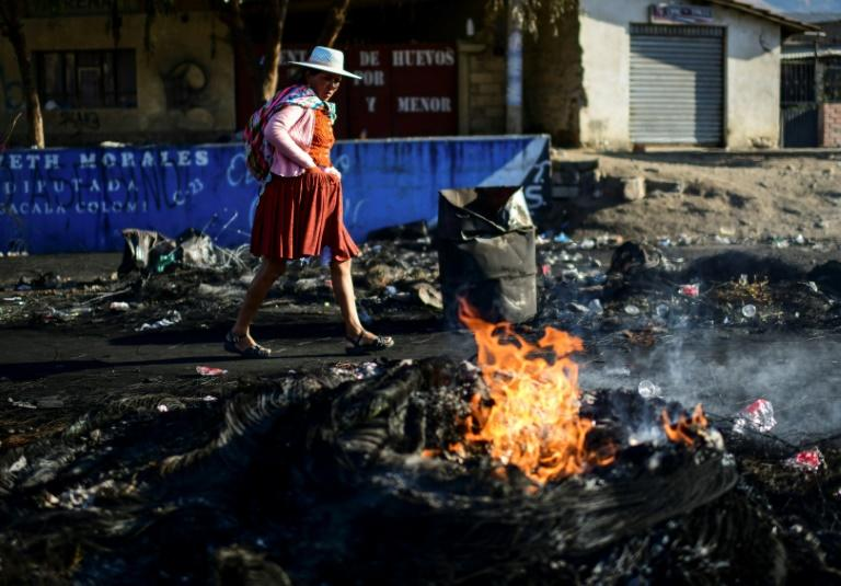 An indigenous woman walks through a blockade -- erected by supporters of Bolivian ex-President Evo Morales -- in the outskirts of Sacaba near Cochabamba