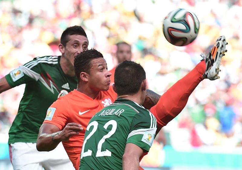 Netherlands' forward Memphis Depay (C) vies for the ball with Mexico's defender Paul Aguilar (R) during a Round of 16 football match between Netherlands and Mexico at Castelao Stadium in Fortaleza during the 2014 FIFA World Cup on June 29, 2014