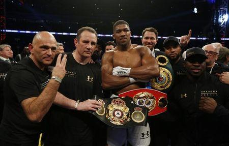 Anthony Joshua celebrates with trainer Robert McCracken, promoter Eddie Hearn and his corner after winning the fight