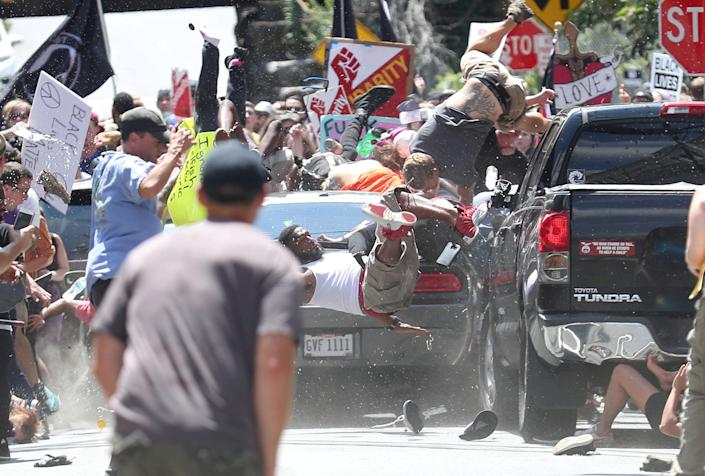 """In this Pulitzer Prize-winning photo, people are thrown into the air as a car plows into a group of protesters demonstrating against a """"Unite the Right"""" rally in Charlottesville, Va., on Aug.12, 2017. (Photo: Ryan M. Kelly/Daily Progress via Reuters)"""
