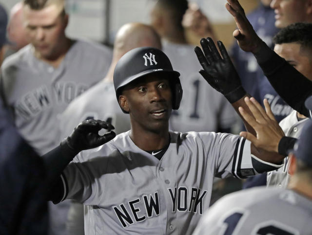 FILE - In this Sept. 7, 2018, file photo, New York Yankees' Andrew McCutchen is greeted in the dugout after he hit a two-run home run during the third inning of a baseball game against the Seattle Mariners, in Seattle. A person familiar with the negotiations tells The Associated Press that All-Star outfielder Andrew McCutchen and the Philadelphia Phillies have agreed to a $50 million three-year contract. The person spoke on condition of anonymity Tuesday, Dec. 11, 2018, because the agreement, which includes a club option for 2022, is subject to a successful physical.(AP Photo/Ted S. Warren, File)