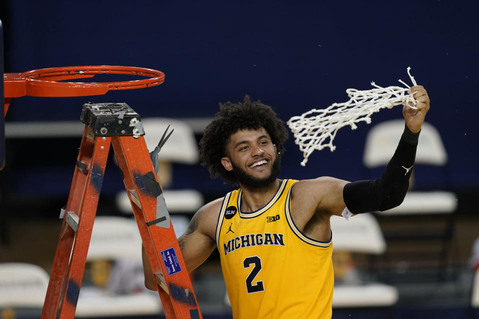 Michigan forward Isaiah Livers twirls the net after the team won the Big Ten title against Michigan State in the second half of an NCAA college basketball game, Thursday, March 4, 2021, in Ann Arbor, Mich. (AP Photo/Carlos Osorio)