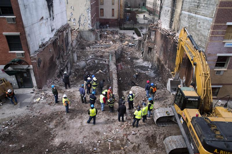 FILE - In this Sunday, March 16, 2014, file photo, workers stand beside the recently cleared basements of two buildings leveled by an explosion last week in the East Harlem neighborhood of New York. A gas main leak has been found at the site of the explosion that killed eight people and leveled two Manhattan buildings, federal investigators said Tuesday, March 18, 2014, but cautioned that they're still a long way from determining what caused the blast. (AP Photo/John Minchillo, File)
