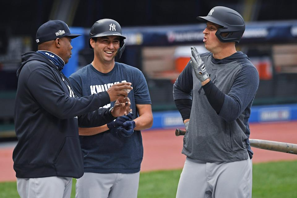 New York Yankees hitting coach Marcus Thames, left, talks with Kyle Higashioka, center, and Erik Kratz before Game 2 of the team's American League wild-card baseball playoff series against the Cleveland Indians, Wednesday, Sept. 30, 2020, in Cleveland.