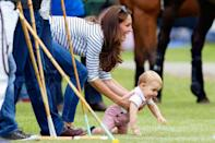 <p>Duchess Kate plays with baby Prince George in the grass while they watch Prince William play in a charity polo match.</p>