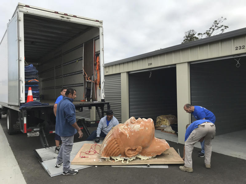 """In this Nov. 8, 2017 photo provided by the Guadalupe-Nipomo Dunes Center, crews move an unearthed sphinx head into safekeeping, where it will be carefully restored in Guadalupe, Calif. Archaeologists working in sand dunes on the central California coast have dug up an intact plaster sphinx that was part of an Egyptian movie set built more than 90 years ago for filming of Cecil B. DeMille's 1923 epic """"The Ten Commandments."""" The 300-pound sphinx is the second recovered from the Guadalupe-Nipomo Dunes. (Guadalupe-Nipomo Dunes Center via AP)"""