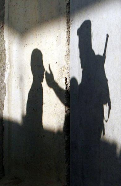 The shadow of a member of the Israeli security forces gesturing towards a Palestinian youth is seen on a wall of a checkpoint on the outskirts of the West Bank town of Bethlehem on July 19, 2013. US Secretary of State John Kerry Friday met with chief Palestinian negotiator Saeb Erakat in a final push to get a peace bid back on track before heading home