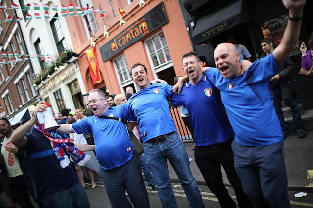 LONDON, ENGLAND - JULY 01: Football fans sing and chant outside the Little Italy bar opposite a Spanish bar ahead of the screening of the UEFA EURO 2012 final football match between Spain and Italy on July 1, 2012 in London, England. London's large Spanish and Italian communities are preparing to watch the final. (Photo by Peter Macdiarmid/Getty Images)