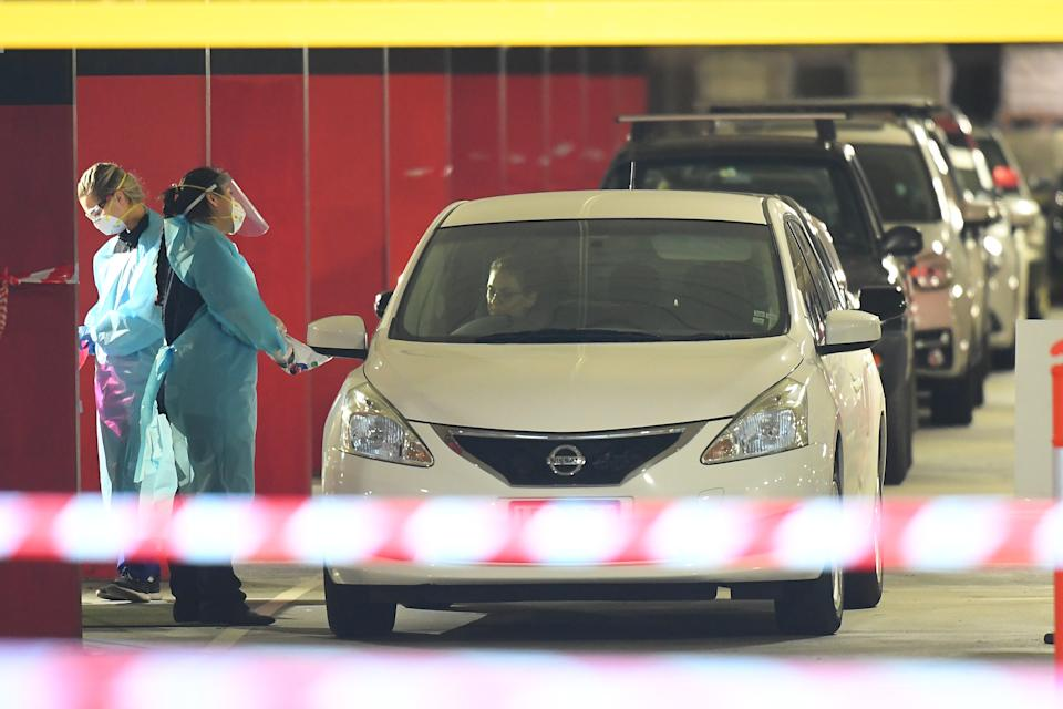 Healthcare employees are seen at work in a Covid-19 testing facility at Northland shopping centre in Melbourne. Source: AAP