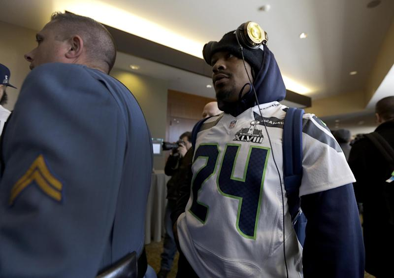 A member of the New Jersey state police escorts Seattle Seahawks running back Marshawn Lynch, right, through an area where a media availability was being held at the team's hotel Wednesday, Jan. 29, 2014, in Jersey City, N.J. The Seahawks and the Denver Broncos are scheduled to play in the Super Bowl XLVIII football game Sunday, Feb. 2, 2014. (AP Photo/Jeff Roberson)