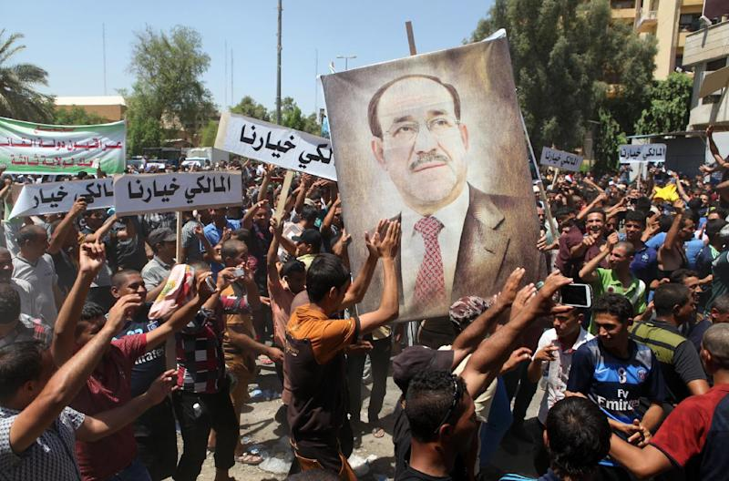Supporters carry a giant portrait of outgoing Iraq Prime Minister Nuri al-Maliki during a demonstration in central Baghdad, August 11, 2014 (AFP Photo/Amer Al-Saedi)